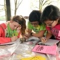 Carley Harris (from left), Mallory Price and Melina Rice write their outdoor stories on May 4 during...