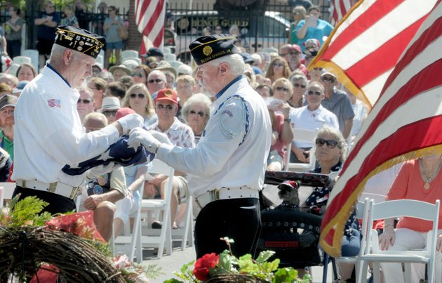 stuart-reeves-left-and-jim-gillig-both-with-siloam-springs-american-legion-post-fold-the-flag-monday-during-the-memorial-day-ceremony-at-fayetteville-national-cemetery-the-ceremony-included-the-traditional-color-presentations-rifle-volley-memorial-wreath-recognition-and-keynote-speaker-retired-col-anita-deason