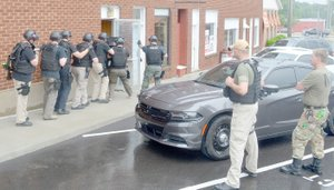 Keith Bryant/The Weekly Vista Bella Vista and Pea Ridge officers attending the departments' joint basic SWAT course enter an out-of-use Bank of Gravett building, while Bella Vista Police Department Lt. Scott Vanatta and Sgt. Eric Palmer observe.