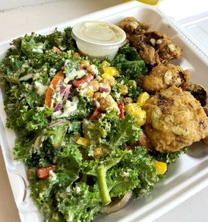 A heaping portion of Kale Salad With Cajun Chickpeas comes with a side, in this case batter-fried cauliflower.