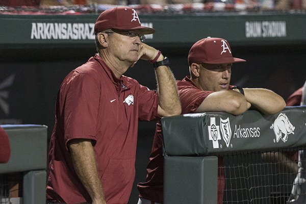 Arkansas head coach Dave Van Horn, left, and pitching coach Wes Johnson watch from the dugout during an NCAA Tournament game against Southern Miss on Saturday, June 2, 2018, in Fayetteville.