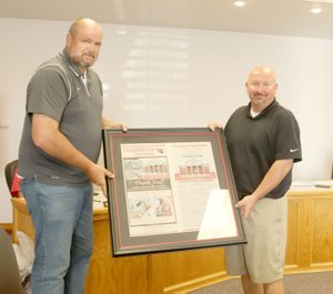 LYNN KUTTER ENTERPRISE-LEADER Farmington School Board President Jeff Oxford, left, presents high school Principal Jon Purifoy with framed pages from a special newspaper section produced by the Enterprise-Leader to celebrate the first 100 days of the new high school building.