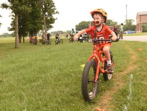 NWA Democrat-Gazette/FLIP PUTTHOFF Sunglasses drop from the nose of Klay Templeton, 4, as he bikes Saturday June 2 2018 along the new trail near Pea Ridge High School. Dozens of bike riders, mostly team members in tne National Interscholastic Cycling Association, formed the trail by riding the route over and over to create a dirt path.