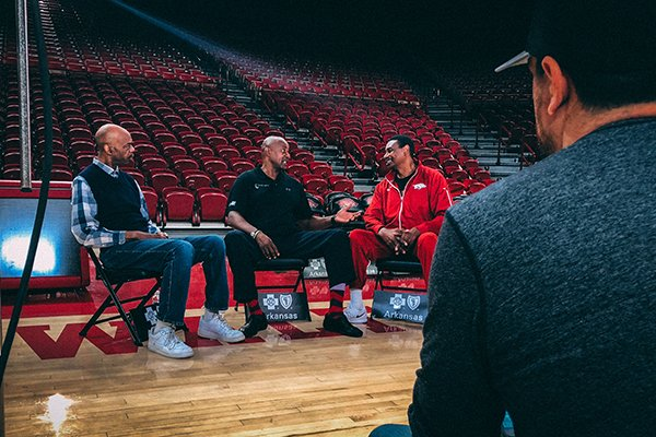"From left to right, former Arkansas basketball players Ron Brewer, Sidney Moncrief and Marvin Delph speak while filmmaker Christopher Hunt, foreground, watches on Wednesday, Feb. 28, 2018, at Bud Walton Arena in Fayetteville. The ""Triplets,"" as the trio is known, were interviewed for a documentary film about their former coach, Eddie Sutton."
