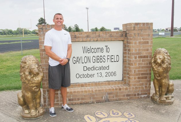 andrew-roberson-the-new-football-coach-at-england-high-school-stands-next-to-the-gaylon-gibbs-field-sign-inside-the-stadium-on-the-school-campus-roberson-was-hired-earlier-this-year-to-replace-matt-garrett-roberson-was-formerly-an-assistant-coach-at-conway-christian-high-school