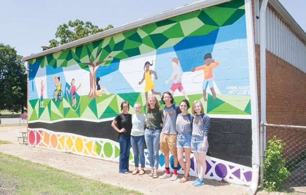 standing-in-front-of-the-new-mural-at-the-searcy-head-start-center-are-director-alicia-cherry-from-left-and-harding-academy-art-club-students-carissa-smith-and-emma-steil-seniors-and-mason-laferney-and-kathryn-wilkins-both-of-whom-graduated-this-year-and-maggie-lake-art-teacher-at-harding-academy-laferney-submitted-the-winning-design-that-art-club-members-painted-the-head-start-staff-is-now-looking-for-volunteers-to-donate-paint-sprayers-and-their-time-to-paint-the-rest-of-the-building-at-610-moss-st