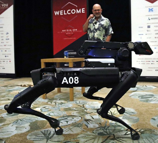 a-boston-dynamics-spotmini-robot-walks-through-a-conference-room-during-a-robotics-summit-in-boston-in-may