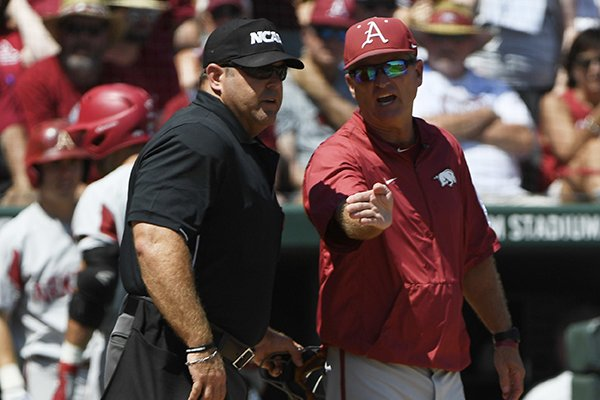 Arkansas coach Dave Van Horn has a word with home plate umpire Mike Morris after a close call at home plate in the third inning of an NCAA college baseball tournament super regional baseball game in Fayetteville, Ark., Sunday, June 10, 2018. (AP Photo/Michael Woods)