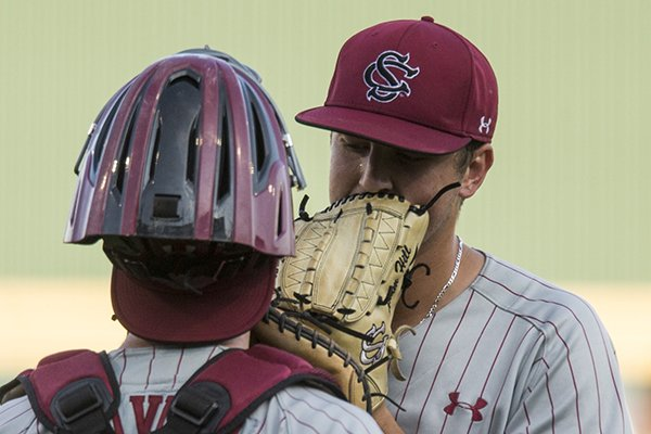 Adam Hill, South Carolina pitcher, confers with catcher Hunter Taylor Saturday, June 9, 2018, during game one of the NCAA Super Regional at Baum Stadium in Fayetteville