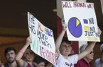 South Carolina fans hold up signs during an NCAA Tournament game against Arkansas on Saturday, June 9, 2018, in Fayetteville.