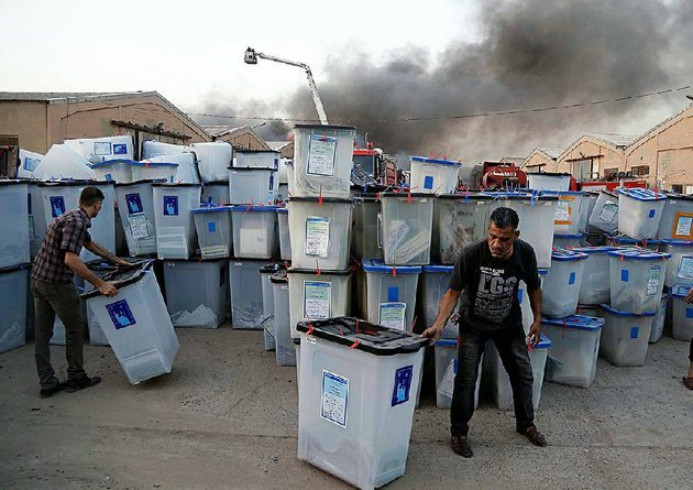 iraqis-work-to-salvage-ballot-boxes-sunday-as-smoke-rises-from-a-fire-that-engulfed-a-baghdad-depot-where-the-ballots-were-being-stored-for-a-recount-the-fire-raised-more-concerns-about-the-legitimacy-of-national-elections-that-were-already-marred-by-fraud-accusations