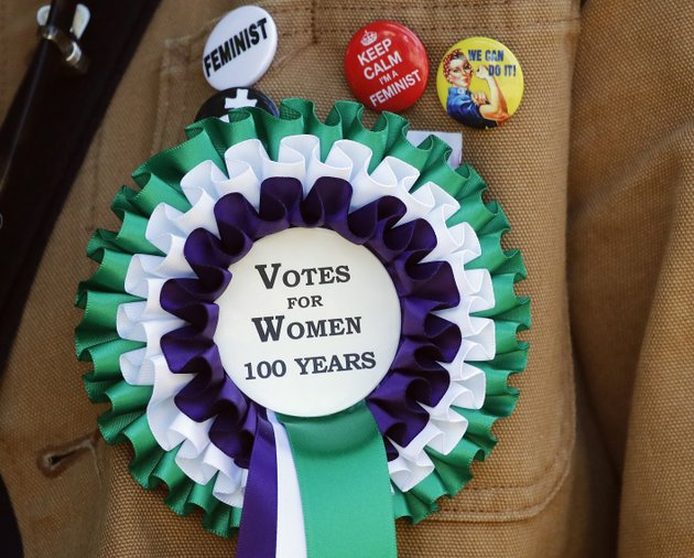 a-participant-wears-a-rosette-as-she-takes-part-in-a-march-through-the-streets-to-celebrate-100-years-since-women-were-granted-the-vote-in-london-sunday-june-10-2018-ap-photofrank-augstein