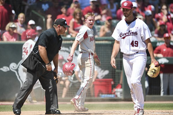Arkansas outfielder Heston Kjerstad (center) and South Carolina pitcher Cody Morris (49) walk off the field after home plate umpire Mike Morris called Kjerstad out during an NCAA Tournament game Sunday, June 10, 2018, in Fayetteville.