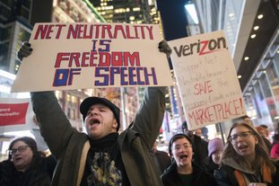 In this December 2017 file photo, demonstrators rally in support of net neutrality outside a Verizon store in New York. Consumers aren't likely to see immediate changes following Monday formal repeal of Obama-era internet rules that had ensured equal treatment for all. Rather, any changes are likely to happen slowly, and companies will try to make sure that consumers are on board with the moves, experts say. (AP Photo/Mary Altaffer, File)
