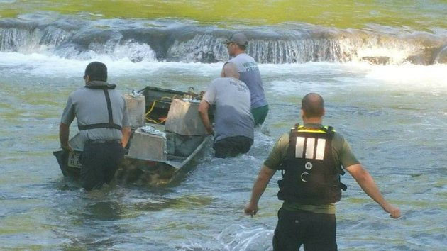 wildlife-officers-from-the-arkansas-game-and-fish-commission-work-to-barricade-the-area-where-a-sinkhole-opened-in-the-spring-river-on-saturday-afternoon-killing-a-kayaker-who-was-sucked-into-a-resulting-whirlpool