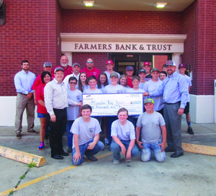 The Magnolia Trap Team is pictured with Farmers Bank officials Monty Harrington (second row, left) and Jason Ray (second row, right) as they present a $1,000 check to the team, on behalf of the local bank.