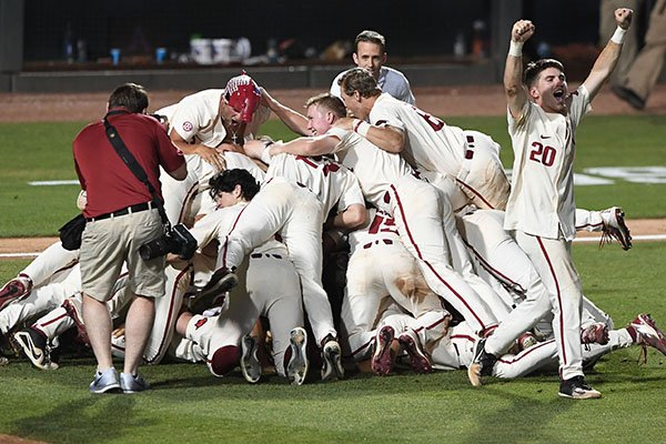 Arkansas players dog pile after defeating South Carolina 14-4 on Monday, June 11, 2018, in Fayetteville. The Razorbacks advanced to the College World Series for the ninth time in program history.