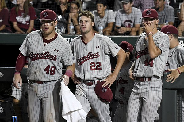 South Carolina players Matt Williams (48) Logan Chapman (22) and Parker Coyne (44) watch Arkansas celebrate during an NCAA college baseball tournament super regional baseball game in Fayetteville, Ark., Monday, June 11, 2018. (AP Photo/Michael Woods)