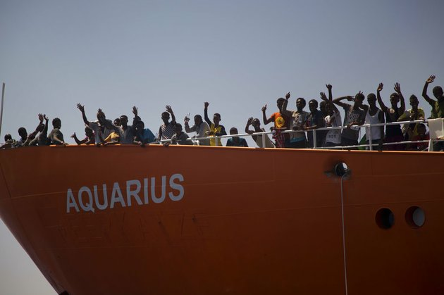 in-this-photo-taken-on-sunday-aug-21-2016-migrants-wave-from-sos-mediterranee-aquarius-rescue-ship-after-being-rescued-by-members-of-the-spanish-ngo-proactiva-open-arms-during-an-operation-at-the-mediterranean-sea-about-12-miles-north-of-sabratha-libya