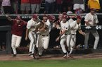 Arkansas players rush the field after recording the final out of an NCAA super regional against South Carolina on Monday, June 11, 2018, in Fayetteville.