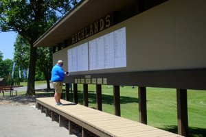 Lynn Atkins/The Weekly Vista Alex Sanford, golf professional at Highlands, posts the Pro-Am scores on the brand new scoreboard recently built by the volunteer organization, Friends of the Highlands on Tuesday of the APT Tournament.