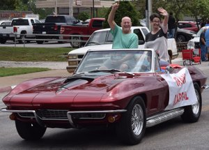 "Westside Eagle Observer/MIKE ECKELS Bill Montgomery (left) and wife Michel greet family and friends as they lead the Decatur Barbecue parade through downtown Decatur August 5, 2017. The parade will return to downtown Decatur August 4 during the 65th Annual Decatur Barbecue. The theme for this year's event is ""Then and Now,"" the history of the Decatur Barbecue."