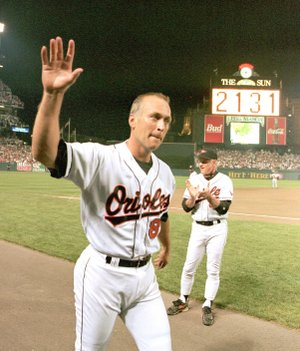 AP Photo/Denis Paquin Baltimore Orioles' Hall-of-Famer Cal Ripken Jr. waves to the crowd as the sign in centerfield reads 2,131, signifying Ripken had broken Lou Gehrig's record of playing in 2,130 consecutive games, at Camden Yards in Baltimore, in this Sept. 6, 1995, photo.