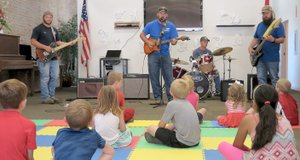 "Westside Eagle Observer/RANDY MOLL Children were treated to some ""rockin' music"" at the opening session of the Gentry Public Library's summer reading program on June 5. The musicians, dubbed by Mayor Kevin Johnston as the Public Works Band, are Chase Shawver (left), Mark Bunce, Jeremy McJunkin and Clint Osborne (on the drums). The band members work for the city of Gentry, in the public works department by day but play music together after hours. They were called in to help kickoff the summer reading program because of its focus on music. The June 5 session focused on types of music, and the band members played a variety of music for their young fans."