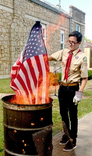 Janelle Jessen/Herald-Leader Avrey Della Rosa, a member of Boy Scout Troop 3766, retired a U.S. flag during a flag retirement ceremony on Saturday evening. The event was conducted by American Legion Post 29, the Sons of the American Legion and the Boy Scout Troop.