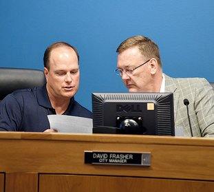 The Sentinel-Record/Grace Brown RESIGNATION TENDERED: Assistant City Manger/City Clerk Lance Spicer, left, speaks with City Manager David Frasher Tuesday at City Hall. The board later convened an executive session and accepted Frasher's resignation.