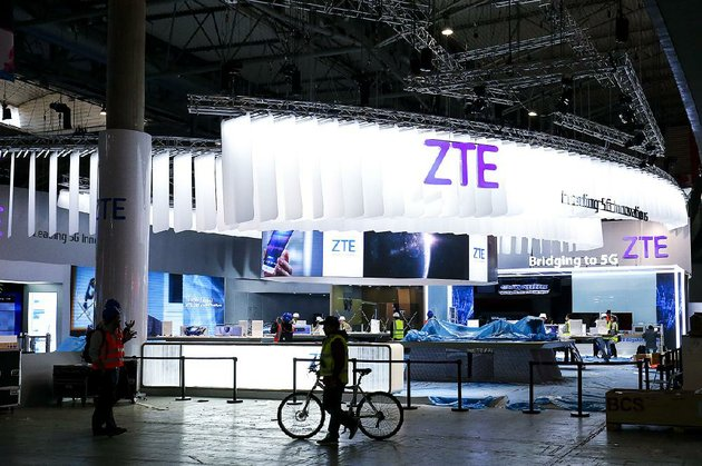 people-mingle-near-the-zte-corp-stand-in-barcelona-spain-in-this-2017-photo-shares-of-the-chinese-technology-company-plunged-40-percent-on-hong-kongs-stock-exchange-wednesday-the-first-day-the-stock-was-traded-since-the-us-government-imposed-heavy-penalties-on-the-company-two-months-ago