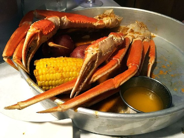 a-pound-of-snow-crab-legs-with-melted-butter-a-corn-cobette-and-two-baseball-size-potatoes-nearly-fill-the-metal-serving-tray-at-the-juicy-seafood