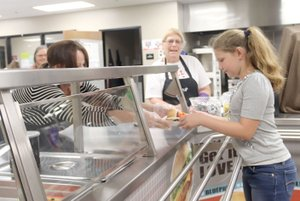LYNN KUTTER ENTERPRISE-LEADER Lesa Owens, food service director with Aramark for Lincoln schools, hands over a free lunch to Hope Lewis, 10, of Cane Hill, last week at Lincoln High School. The meal this day was BBQ rib sandwich, sweet carrots, watermelon slice and milk. Cafeteria worker Star Griscom, center, also helps in the kitchen.