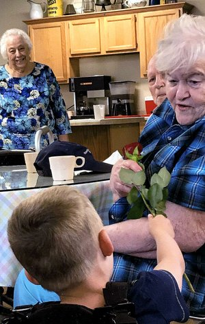 COURTESY PHOTO/Four-year-old Zane Smythia, grandson of Frank and Carolyn Williams, hands out fresh roses to the women at the Noel Senior Center on Mother's Day. The Williams' brought Zane to the center to visit with the ladies and learn about the art of giving.
