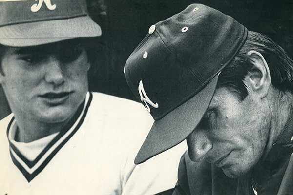 Arkansas coach Norm DeBriyn, right, looks toward the ground while catcher Ronn Reynolds watches during a College World Series game against Cal State Fullerton on Friday, June 8, 1979, in Omaha, Neb.