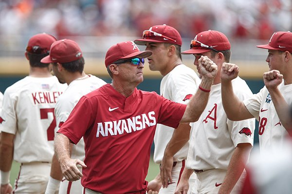 Arkansas coach Dave Van Horn greets his players prior to a College World Series game against Texas on Sunday, June 17, 2018, in Omaha, Neb.