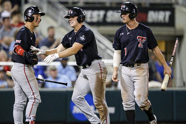 Texas Tech's Cody Farhat, right, and Braxton Fulford, center, are congratulated by Brian Klein after they scored against Florida on a two-run single by Gabe Holt in the fifth inning of an NCAA College World Series baseball game in Omaha, Neb., Sunday, June 17, 2018. (AP Photo/Nati Harnik)