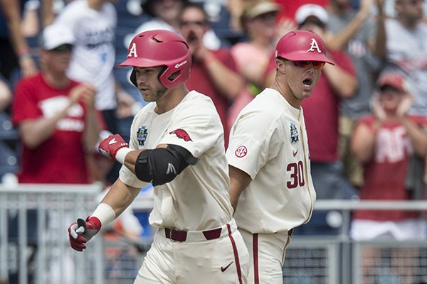nate-thompson-arkansas-assistant-coach-congratulates-luke-bonfield-as-he-rounds-thrid-after-hitting-a-two-run-homer-in-the-5th-inning-vs-texas-sunday-june-17-2018-during-game-three-of-the-ncaa-mens-college-world-series-at-td-ameritrade-park-in-omaha