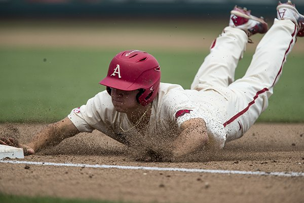 Arkansas' Jared Gates slides into third base during a College World Series game against Texas on Sunday, June 17, 2018, in Omaha, Neb.