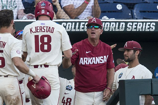 Arkansas coach Dave Van Horn greets Heston Kjerstad (18) after he scored a run during the sixth inning of a College World Series game against Texas on Sunday, June 17, 2018, in Omaha, Neb.