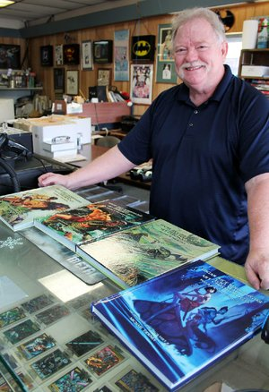 Michael Tierney, owner of Collector's Edition Comics in North Little Rock and The Comic Book Store in Little Rock, shows off his four-volume Edgar Rice Burroughs 100 Year Art Chronology.