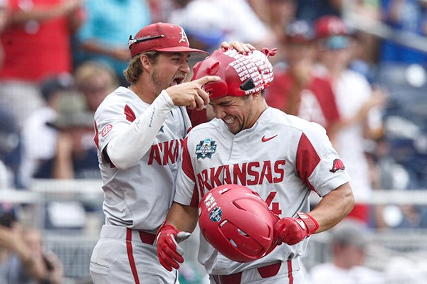 Arkansas infielder Hunter Wilson, left, puts a Hog hat on the head of outfielder Dominic Fletcher after Fletcher hit a home run during the fourth inning of a College World Series game against Texas Tech on Wednesday, June 20, 2018, in Omaha, Neb.