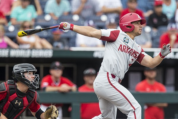 Dominic Fletcher, Arkansas center fielder, hits a 2 RBI double in the 1st inning as Braxton Fulford catches for Texas Tech Wednesday, June 20, 2018 in game eight of the NCAA Men's College World Series between at TD Ameritrade Park in Omaha.
