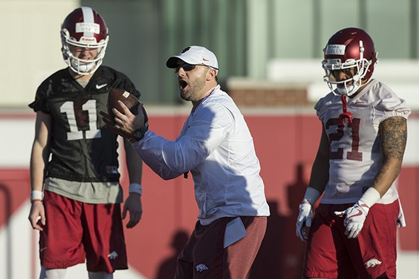 Arkansas offensive coordinator Joe Craddock (center) instructs while quarterback Daulton Hyatt (11) and running back Devwah Whaley (21) watch during practice Thursday, March 1, 2018, in Fayetteville.