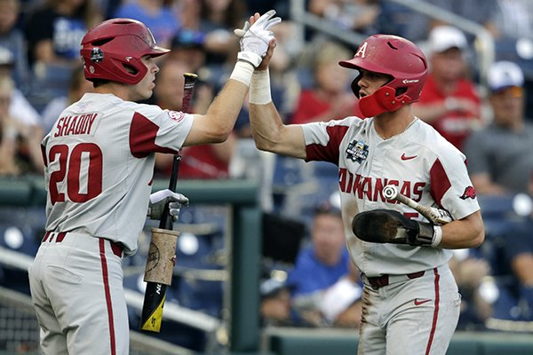 Arkansas' Casey Martin, right, high-fives teammate Carson Shaddy (20) after scoring against Florida on an RBI-single in the first inning of an NCAA College World Series baseball game in Omaha, Neb., Friday, June 22, 2018. (AP Photo/Nati Harnik)