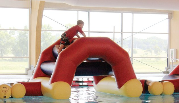 ethan-orsburn-7-of-russellville-moves-carefully-through-the-inflatable-obstacle-course-at-the-russellville-aquatic-center-the-66-million-facility-opened-a-year-ago-on-june-28-and-has-added-programming-and-activities-since-then-the-obstacle-course-was-purchased-this-summer