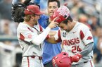Arkansas infielder Hunter Wilson, left, places a Hog hat on outfielder Dominic Fletcher after Fletcher hit a home run during a College World Series game against Florida on Friday, June 22, 2018, in Omaha, Neb.