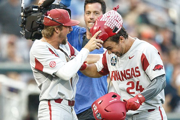 arkansas-infielder-hunter-wilson-left-places-a-hog-hat-on-outfielder-dominic-fletcher-after-fletcher-hit-a-home-run-during-a-college-world-series-game-against-florida-on-friday-june-22-2018-in-omaha-neb