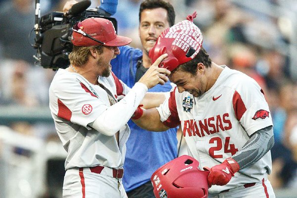 Arkansas' Dominic Fletcher (right) is presented the home run hog hat by Hunter Wilson after he hit a home run in the Razorbacks' victory over Florida on Friday night at the College World Series. The Hogs open play in the best-of-three championship series Monday.