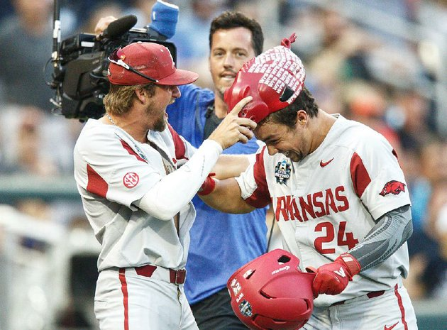 arkansas-dominic-fletcher-right-is-presented-the-home-run-hog-hat-by-hunter-wilson-after-he-hit-a-home-run-in-the-razorbacks-victory-over-florida-on-friday-night-at-the-college-world-series-the-hogs-open-play-in-the-best-of-three-championship-series-monday